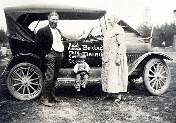 Photo of Harry and Louisa Buzby with very young Jim Spencer, and their car with 'Buzby's Dairy, real buttermilk, milk, cream, eggs' painted on the side.