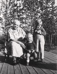 Louisa Buzby and grandchildren Robbie Gleason and Sammy Buzby sitting outside on the porch.