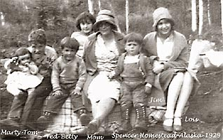 Black and white photo of Bessie Spencer and her children, sitting in a row on a large log at their Alaska homestead, 1929